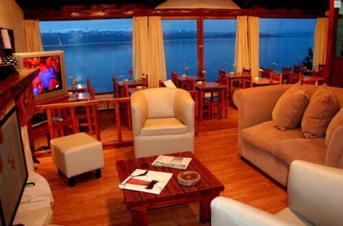 hosteria costas del nahuel bariloche sala de estar sofas vista al lago por ventanales