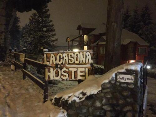 La Casona Hostel Bariloche - cartel de entrada frente invierno con nieve